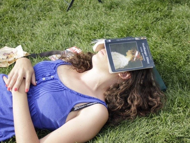 woman sleeping on grass reading
