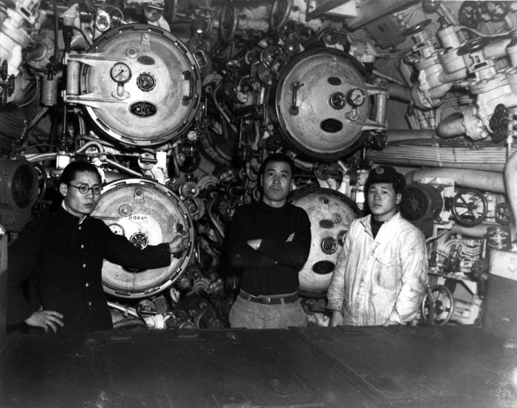 View in the forward torpedo room, showing 21-inch torpedo tubes and three crew members. Taken at Sasebo, Japan, 28 January 1946. This submarine torpedoed and sank USS Indianapolis (CA-35) on 30 July 1945.